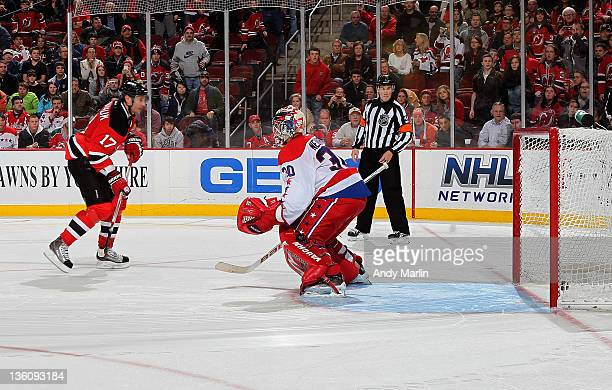 Ilya Kovalchuk of the New Jersey Devils puts the puck behind Michal Neuvirth of the Washington Capitals for the game deciding goal in the shootout at...