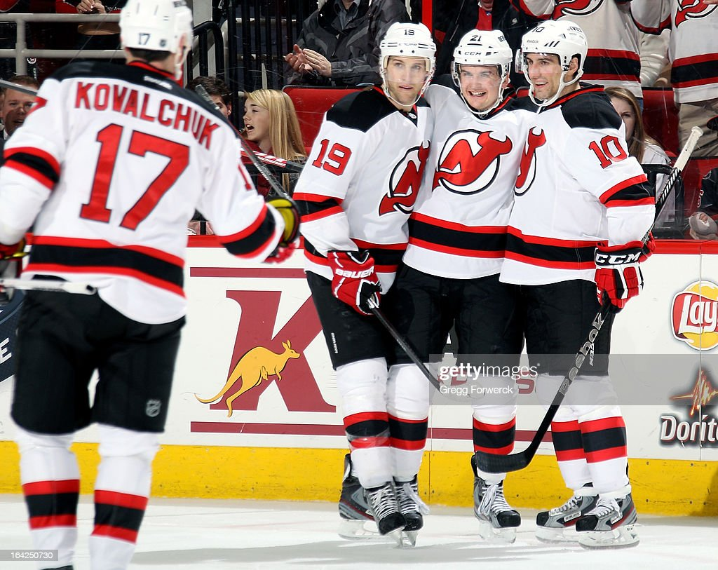 Ilya Kovalchuk #17 of the New Jersey Devils skates in to celebrate with teammates Travis Zajac #19 and Peter Harrold #10 following a goal scored by Andrei Loktionov #21 against the Carolina Hurricanes during their NHL game at PNC Arena on March 21, 2013 in Raleigh, North Carolina.