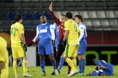 Ilya Maksimov of FC Anji is shown a red card by referee Alon Yefet during the Europa League round 32 first leg match between FC Anji Makhachkala and...
