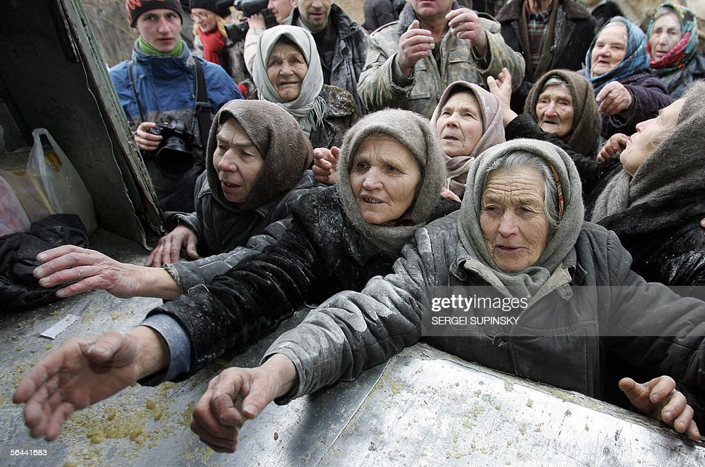 Ukraine Emergencies Ministry personnel give out sacks of flour to residents of the Ilyintsy village, a closed zone around the Chernobyl nuclear power plant, about 100 km from Kiev, 16 December 2005. More than 330 mostly elderly people have chosen to return and live in the villages illegaly around the power plant, which was the site of the world's worst civilian nuclear disaster in 1986. President Viktor Yushchenko, who visited Chernobyl last week, called for Ukrainian regions to provide humanitarian assistance to the residents around Chernobyl, who live in poverty. AFP PHOTO/ SERGEI SUPINSKY