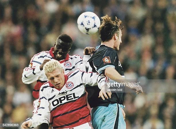 Im Münchener Lokalderby zwischen dem FC Bayern und dem TSV von 1860 springt eine Spielertraube zum Kopfball hoch Thomas Strunz und Sammy Kuffour...
