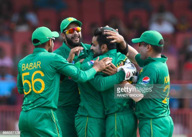 Imad Wasim and teammates hug Mohammad Hafeez of Pakistan celebrating the dismissal of Jason Mohammed of West Indies during the 2nd ODI match between...