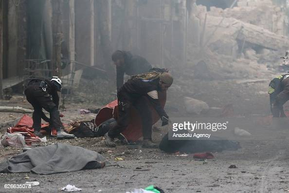 Image depicts death] Syrian Civil defense team members are seen at the impact site after war crafts belonging to the Assad Regime forces carried out...
