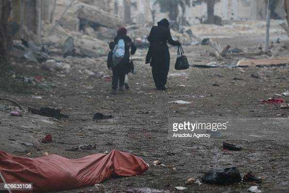 Image depicts death] Syrian women leave the impact site after war crafts belonging to the Assad Regime forces carried out airstrikes over residential...