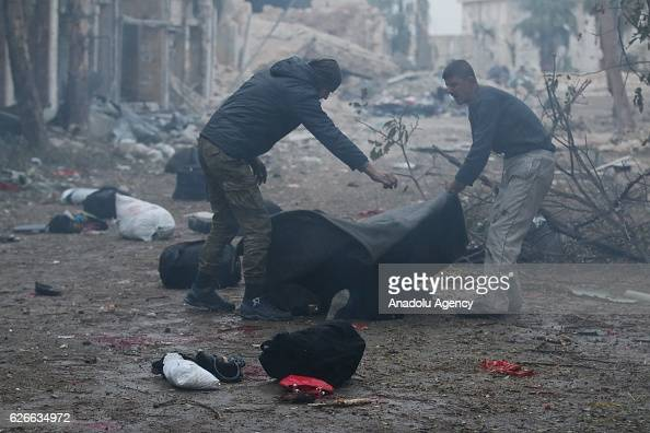 Image depicts death] Syrians try to carry a dead body after war crafts belonging to the Assad Regime forces carried out airstrikes over residential...
