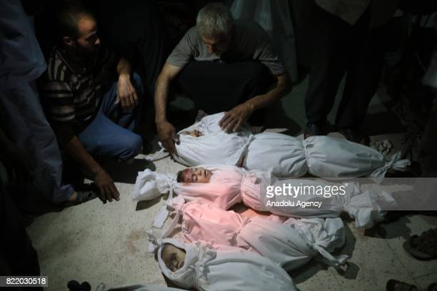 Image depicts death] Syrians wait around the bodies of children after Assad Regime's forces carried out airstrike over the deconflict zone Arbin town...