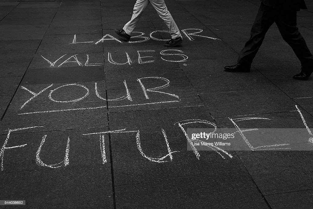 Image has been shot in black and white, no colour version available.) Commuters walk by a Labor Party message on the ground during a Medicare Rally at Martin Place on July 1, 2016 in Sydney, Australia.Bill Shorten is campaigning heavily on Medicare, promising to make sure it isn't privatised if the Labor Party wins the Federal Election on July 2.