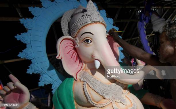 Image makers busy to apply colors into the clay images of elephant headed God Ganesha ahead of the Ganesha Chatruthi festival at a village outskirts...