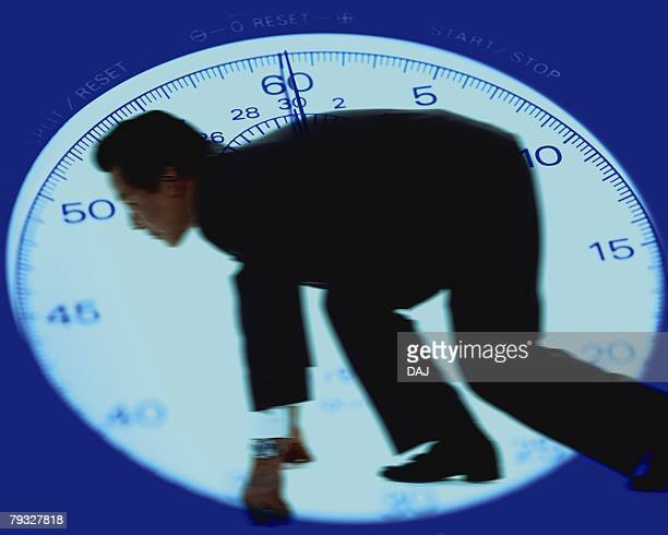 Image of a Businessman About to Sprint, a Stopwatch in his Background, CG, Differential Focus