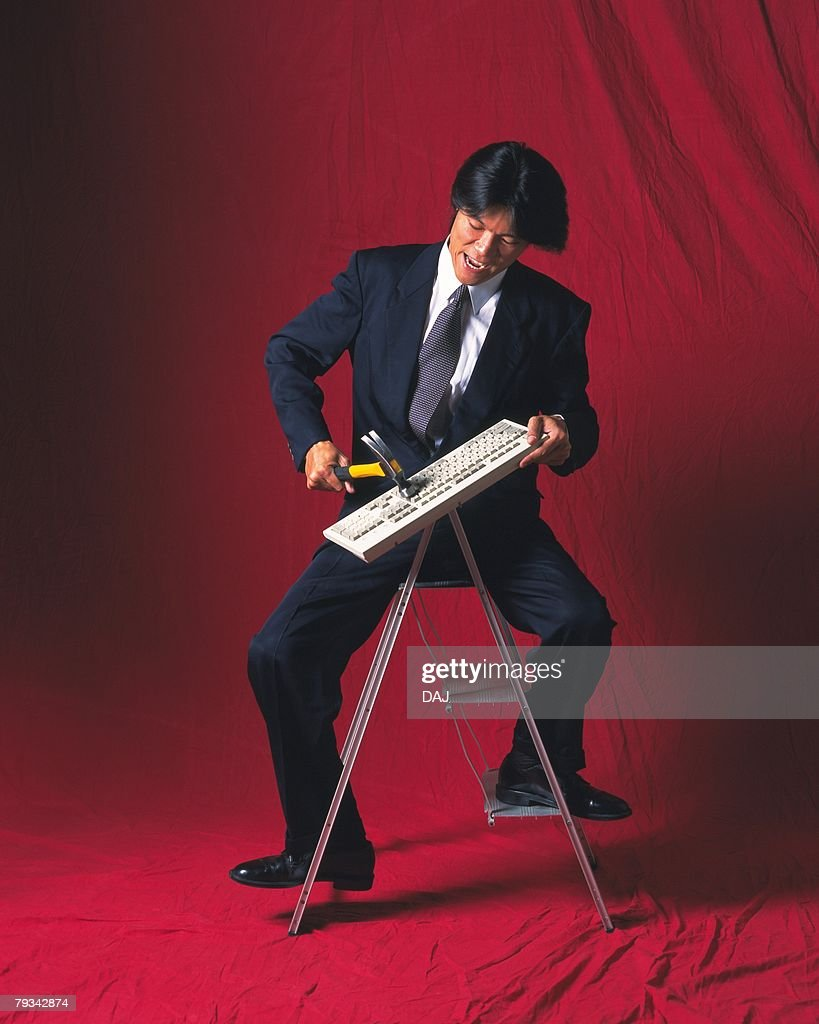 Image of a Businessman Sitting on a Stepladder, Breaking a Keyboard With a Hammer, Front View