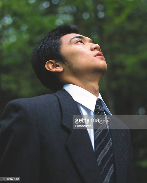 Image of a Businessman Surrounded By Green, Looking Up, Low Angle View, Side View, Differential Focus