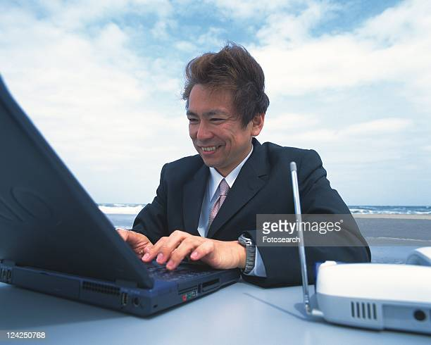 Image of a Businessman Working on his Laptop at the Beach, Smiling, Side View