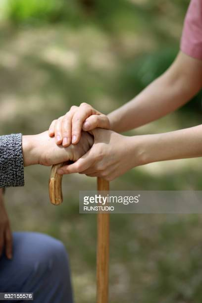 Image of a female nurse holding a patient's hand