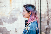 Image of a girl with colorful hair standing next to an old wall.