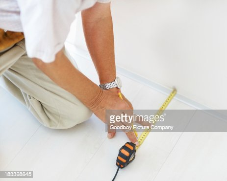 Image of a handyman taking floor measurements