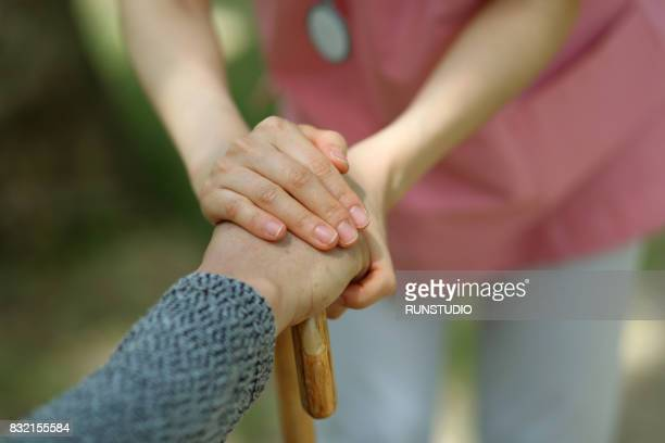Image of a nurse holding the hand of an old man