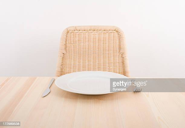 Image of a single plate with an empty seat at a table