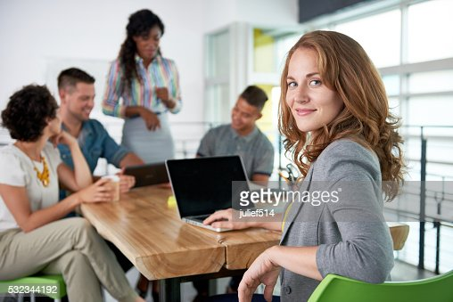 Image of a succesful casual business woman using laptop during : Stock Photo