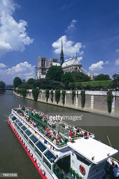 Image of a Tourist Boat On the Seine on a Clear Day, the Notre Dame de Paris in the Background, High Angle View, Side View, Paris, France