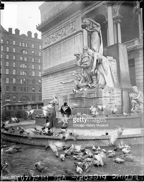Image of a woman and man feeding pigeons standing in front of the Fountain of the Great Lakes designed by Lorado Taft in front of the south face of...