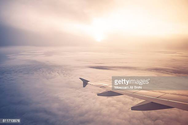 Image of airplane wing flying above the clouds