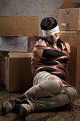 A young woman tied-up, blind folded and muted in old room. Low key setting