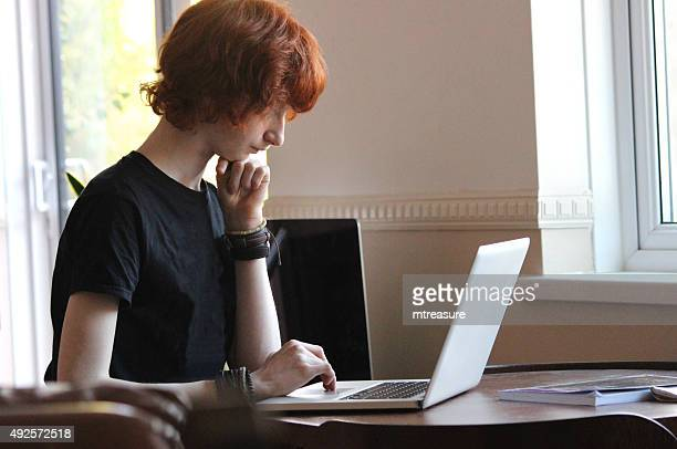Image of boy surfing Internet on laptop-computer for school homework