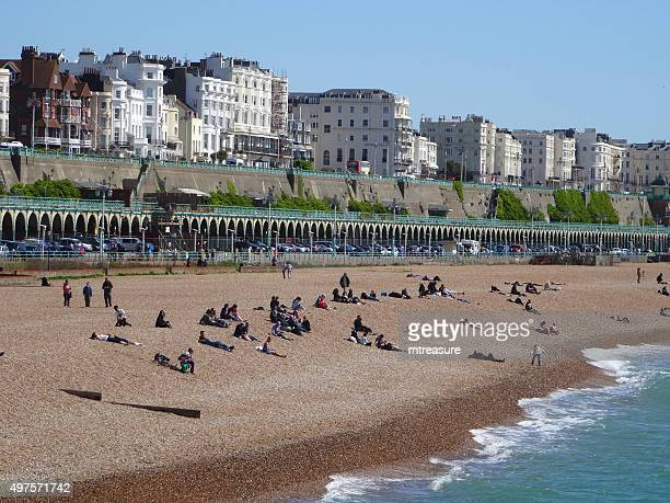 Image of busy beach in Brighton with sunbathers / seafront promenade