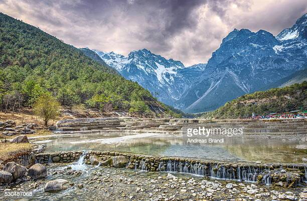 HDR image of cascading falls at Baishuihe, or White Water River with Jade Dragon Snow Mountain, Lijiang, Yunnan, China, Asia