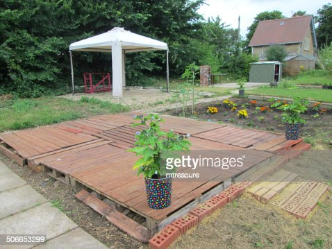 Image of cheap decking in garden made from wooden pallets for Cheapest place for decking