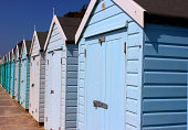 Photo showing colourful English beach huts, painted in graduating bright rainbow colours.  This stretch shows the greens, turquoises and blues.  The beach huts are photographed against the cliff backd