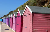 Photo showing colourful English beach huts, painted in graduating bright rainbow colours.  This stretch shows the reds, purples and blues.  The beach huts are photographed against the cliff backdrop a