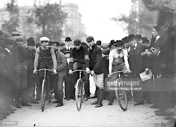 Image of cyclists J E Gill C A Linde Ed Bukowski positioning on their bicycles in front of a crowd on North Michigan Avenue in the Near North Side...
