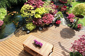 Photo showing a landscaped contemporary Japanese garden with a large expanse of pre-treated timber decking, providing a family space for outdoor furniture - a modern slatted table and benches.  The st