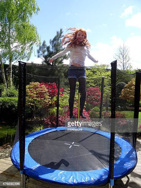 Image of girl playing in garden, bouncing on round trampoline