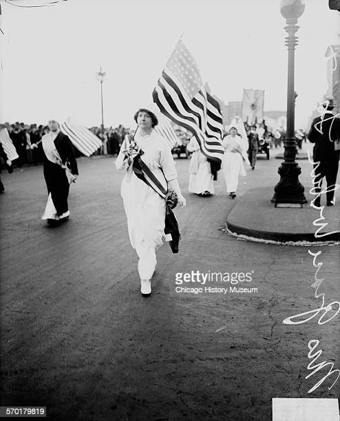 Image of Grace Wilbur Trout wearing a sash holding an American flag marching north on South Michigan Avenue with other suffragists holding flags...