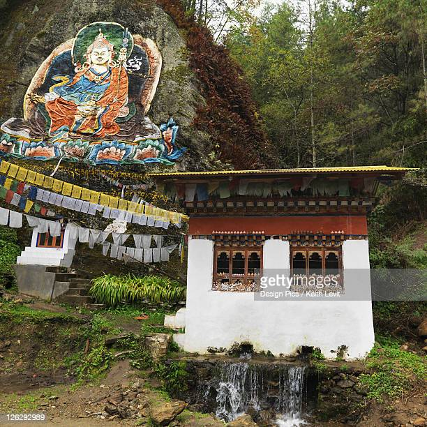 image of guru rimpoche above prayer flags and a building