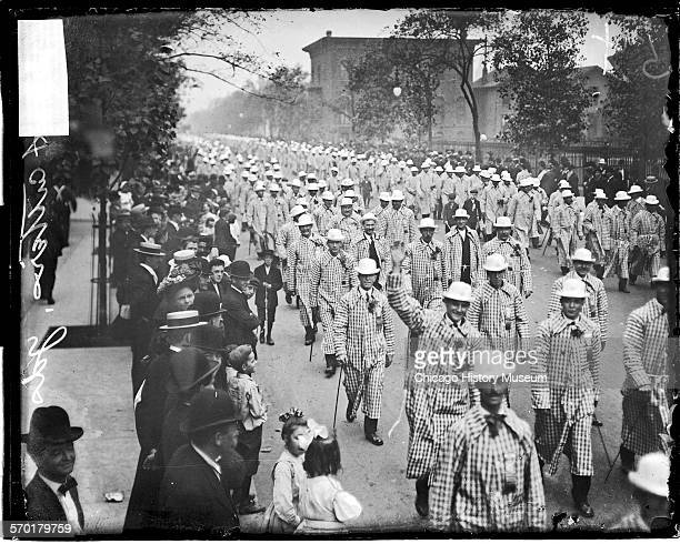 Image of meat cutters wearing checkered overcoats marching in a Labor Day parade in Chicago Illinois 1900s Text on the negative reads Meat Cutters...