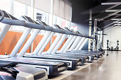 Image of empty gym and treadmills in it.