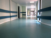Photo showing a colourful hospital corridor, with turquoise and blue vinyl flooring, floor to ceiling windows overlooking gardens, and a row of strip lights within the ceiling tiles. Various medical t