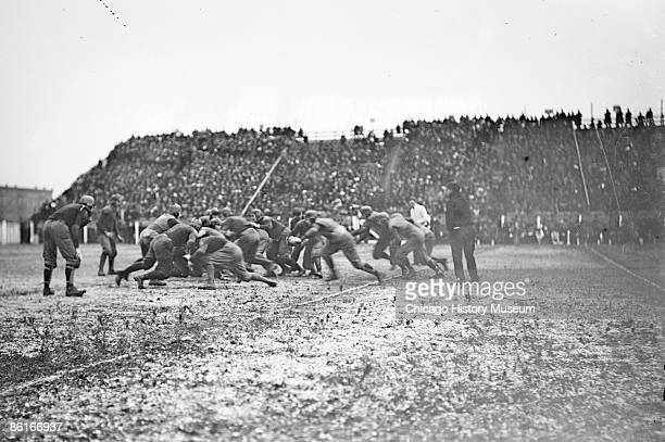 Image of opposing offensive and defensive lines pushing toward center of play during a University of Chicago versus University of Michigan football...
