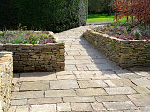 Photo showing a sunken garden with raised beds made from dry-stone walls and a patio of flagstone paving.  The garden is designed to be accessible for gardeners in wheelchairs, with the sloped pathway