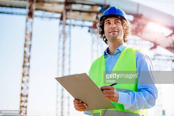 Image of successful engineer near the bridge construction platform