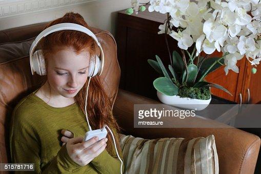Image of teenage girl listening to music on large headphones