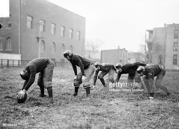 Image of three Waller High School football running backs crouching in position behind the center and quarterback on a field in Chicago Illinois 1902...