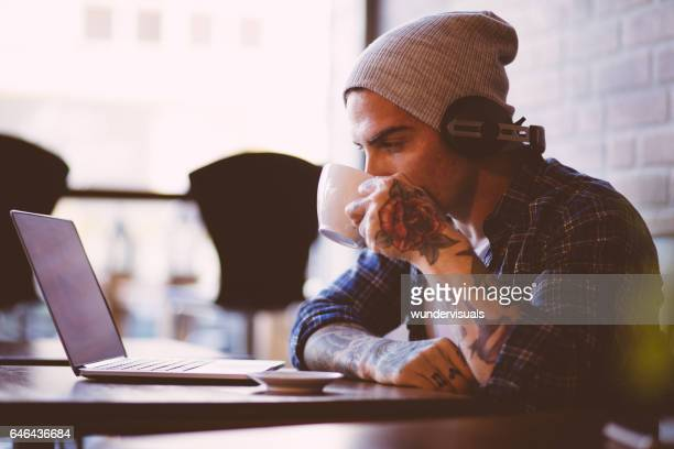 Image of trendy man with headphones, laptop and coffee