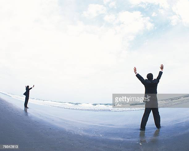 Image of Two Businessmen With Arms Wide Open Towards the Ocean, Rear View, Fish Eye