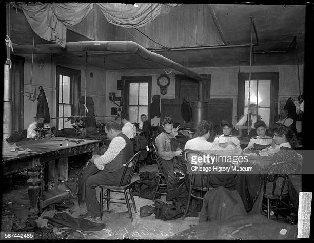 Image of women and men sewing at various tables and sewing machines in the workroom of a sweatshop at 132 Maxwell Street in the Near West Side...