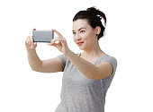Image of young woman standing isolated on white background looking aside make selfie or video chat by smartphone.