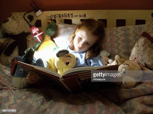 画像の若い女性の読書童話のベッド、動物のおもちゃ